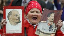 A woman shouts as she carries portraits of Lenin and Stalin during a Communist Party rally to mark May Day in Moscow, Tuesday, May 1, 2012. (Mikhail Metzel/Mikhail Metzel / AP)