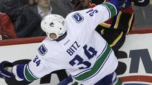 Vancouver Canucks' Bryon Bitz (L) crashes with Calgary Flames' Tim Jackman during second period action in their NHL hockey game in Calgary, Alberta, April 5 , 2012. (JACK CUSANO/REUTERS)