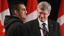 Prime Minister Stephen Harper, right, stands with former gang member Tanbir Uppal after announcing the renewal of the Youth Gang Prevention Fund. in Surrey, B.C., on Tuesday March 15, 2011. (DARRYL DYCK/Darryl Dyck/THE CANADIAN PRESS)