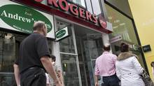 People walk past a Rogers store in Montreal on Tuesday, June 26, 2012. (Ryan Remiorz/The Canadian Press)
