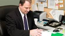 At desk in office with file (Jupiterimages/www.jupiterimages.com)