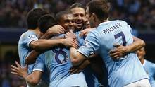 Manchester City's Fernandinho, centre, celebrates with team mates after scoring a goal against Arsenal during their English Premier League soccer match at the Etihad stadium in Manchester on Dec. 14, 2013. (DARREN STAPLES/REUTERS)