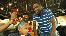 Chris Rock talks to a young African-American girl having her hair straightened.