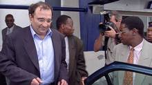 Ari Ben Menashe is hustled into a car by Zimbabwean security personnel shortly after his arrival in Harare on Feb. 22, 2002. (Associated Press)
