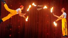 Performers Joshua Phillips (L) and Idris Stanton (R) juggle fire together. (WILLIAM WEST/AFP/Getty Images)