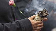 A native woman burns sweet grass during a protest outside the Missing Women's Inquiry in Vancouver, June 6, 2012. The inquiry probed why it took so long to catch serial killer Robert Pickton, who is believed to have killed more than 20 women before he was arrested in 2002. (ANDY CLARK/REUTERS)