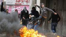 A Palestinian youth throws a stone at Israeli soldiers during a rally to support President Mahmoud Abbas on Monday. (MUSSA ISSA QAWASMA/REUTERS)