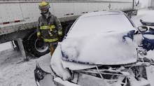 A firefighter checks the scene of a multi-vehicle pileup on Highway 401 westbound between Glen Miller Road and Wallbridge-Loyalist Road near Trenton, Ont. on Wednesday, Feb. 5, 2014.