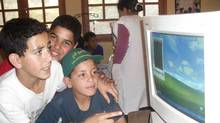 Moroccan children share a donated computer.