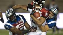 Calgary Stampeders Jon Cornish is taken down by Montreal Alouettes cornerback Billy Parker, left, and Chip Cox during fourth quarter CFL action Friday, July 12, 2013 in Montreal. (Paul Chiasson/THE CANADIAN PRESS)