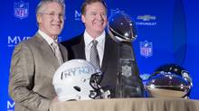 Roger Goodell, commissioner of the National Football League, center, and Pete Carroll, head coach of the Seattle Seahawks, pose for a photograph beside the Vince Lombardi and MVP trophy during a news conference at the Super Bowl XLVIII Media Center at the Sheraton hotel, Monday, Feb. 3, 2014, in New York. (John Minchillo/AP)