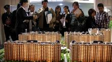 Potential buyers read brochures and talk to sales staff in front of a model depicting a new housing estate at the Beijing Property Trade Fair. (REUTERS/David Gray)