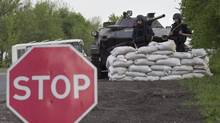 Members of the Ukrainian security services stand near a armoured personnel carrier at a checkpoint near the town of Slavyansk, east Ukraine, on May 1, 2014. (BAZ RATNER/REUTERS)