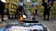 Protesters display placards and a replica of the disputed Scarborough Shoal in the South China Sea as they burn an effigy of a U.S. submarine USS North Carolina, currently on a port call in the country, during a rally at the U.S. embassy in Manila, on May 17. (Bullit Marquez/AP/Bullit Marquez/AP)