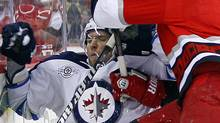 Carolina Hurricanes' Bryan Allen (5) knocks Winnipeg Jets' Blake Wheeler (26) off the puck during the first period of an NHL hockey game in Raleigh, N.C., Friday, March 30, 2012. (AP Photo/Karl B DeBlaker) (Karl B DeBlaker/AP)