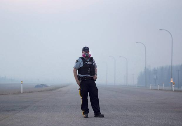 An RCMP officer wears a gas mask to combat the smoke as he mans a checkpoint on the highway to Fort McMurray, Alberta on Friday, May 6, 2016.