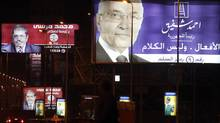 People walk under giant campaign election billboards of presidential candidates former prime minister Ahmed Shafiq (R), and Mohamed Mursi, the head of the Muslim Brotherhood's political party in Cairo May 25, 2012. Egyptians must choose between a Muslim Brother or an ex-military man in a presidential run-off that highlights the stark rifts in a nation united in euphoria when Hosni Mubarak fell 15 months ago, first-round results indicated on Friday. With most votes counted, the Muslim Brotherhood said its candidate Mohamed Mursi had topped this week's polls and would compete in next month's second round with former air force chief Ahmed Shafiq, who served as Mubarak's last prime minister. (Amr Abdallah Dalsh/Reuters/Amr Abdallah Dalsh/Reuters)