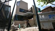 A person wearing a hard hat walks away from 16 Lyndhurst Court in Toronto on May 10, 2012. The mansion large home being built in the Bathurst and Davenport area is being built for Luigi Lusi, an Italian Senator and his wife, Giovanna Petricone, a Canadian citizen who is under arrest in Italy so she won't flee the country. Senator Luigi Lusi is accused of embezzling 22 million Euros from a political party for which he served as treasurer. (Deborah Baic/The Globe and Mail)