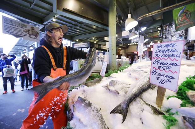 A fishmonger tosses a fresh salmon at the Pike Place Fish Market.
