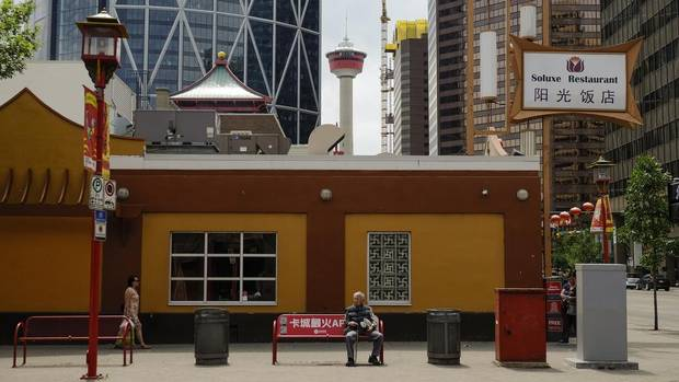 A man rests on a bench in Calgary's Chinatown.