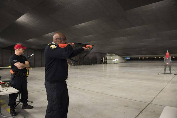 Toronto Police Chief Mark Saunders aims one of the department's new converted shotguns that shoot beanbag projectiles.