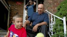 Blair Dimock (right) sits on the steps of his Toronto home with his twin thirteen year old sons Cameron (left) and Malcom (centre) on Sept. 13, 2011. (Chris Young for The Globe and Mail/Chris Young for The Globe and Mail)