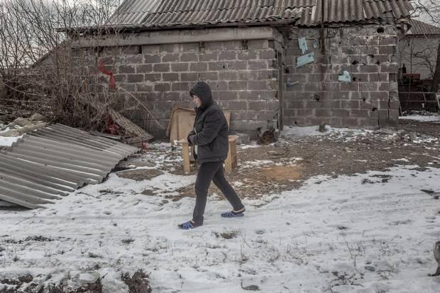 Nina Zharkova walks in her recently shelled backyard in Sartana.