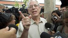 The chairman of Montreal, Maine and Atlantic Railway, Edward Burkhardt, addresses questions from the media in Lac-Mégantic, Que., on July 10, 2013, before leaving with investigators. (Peter Power/The Globe and Mail)