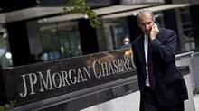 A man walks past JP Morgan Chase & Co.'s international headquarters in New York in this file photo. Regulators Monday ordered the bank to improve its compliance with the Bank Secrecy Act and anti-money laundering requirements, as well as risk controls. (ANDREW BURTON/REUTERS)