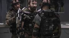 "This film publicity image released by TriStar, Columbia Pictures-Sony shows Sharlto Copley, center, in a scene from ""Elysium."" (Kimberley French/AP)"