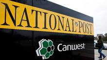 A pedestrian walks past the front of the National Post sign in Toronto on Feb. 27, 2009. Winnipeg-based Canwest, carrying a $3.9-billion debt load overall, is riding a deadline for renegotiating terms of a debt that represents a small portion of its total debt. (NATHAN DENETTE/Nathan Denette / CP)