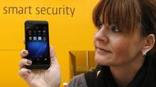 A woman poses with a BlackBerry Z10 smartphone featuring high security Secusite software, in Hanover, March, 4, 2013. BlackBerry and other major smartphone platforms – including Apple's iOS and Windows Phone – each had less than 1 per cent of malware infections. (FABRIZIO BENSCH/REUTERS)