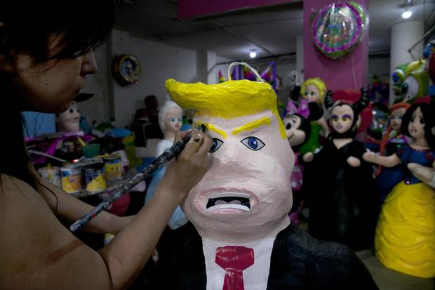 Alicia Lopez Fernandez paints a pinata depicting Donald Trump at her family's store