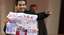 "Actor Eli Roth gestures as he holds a banner reading ""Eli... the king of the red carpet"", which he had received from fans, on the ""A Dangerous Method"" red carpet at the 68th Venice Film Festival Sept. 2, 2011. (Alessandro Garofalo/REUTERS)"