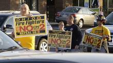 A group of fire fighters urge passing motorists to vote no on Issue Two in Tuesday's election, Monday, Nov. 7, 2011, in Cincinnati, near a hotel where Ohio Gov. John Kasich spoke in support of the issue. (Al Behrman/AP/Al Behrman/AP)