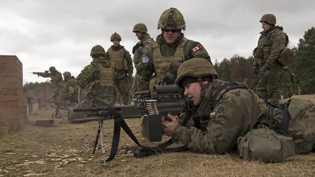 A Canadian Armed Forces member looks on as a Polish soldier fires a C9 machine gun at a training area in Poland March 15, 2016.