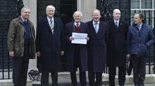Senior local Conservatives pose for a photograph with a letter addressed to Britain's Prime Minister David Cameron, before handing it in, in Downing Street in central London Feb. 3, 2013. Members of Cameron's Conservative party urged him on Sunday to delay a parliamentary vote this week on gay marriage, warning the issue could weaken the party and harm his chances of re-election. A letter signed by more than 20 chairmen of local Conservative associations was handed in to Cameron's Downing Street residence on Sunday afternoon. (TOBY MELVILLE/REUTERS)