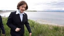 Alberta Premier Alison Redford walks past the Gleniffer reservoir, with an oil retaining boom across it, after speaking with reporters about an oil spill from a pipeline leak near Sundre, Alta. on Friday, June 8, 2012. (Jeff McIntosh/THE CANADIAN PRESS)