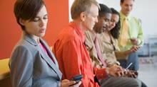 Office staff with cell phones (Jupiterimages/www.jupiterimages.com)