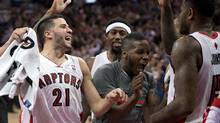 Toronto Raptors' Amir Johnson (right), who made the game winning shot, is congratulated by teammates Greivis Vasquez and Dwight Buycks (The Canadian Press)