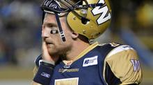 Winnipeg Blue Bombers quarterback Alex Brink walks to the bench after turning the ball over to the Montreal Alouettes during the second half of their CFL game in Winnipeg, August 3, 2012. (FRED GREENSLADE/REUTERS)