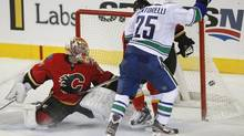 Vancouver Canucks' Mike Santorelli, right, scores the game winning goal on Calgary Flames goalie Joey Macdonald during overtime NHL action in Calgary, Alta., Sunday, Oct. 6, 2013. The Vancouver Canucks beat the Calgary Flames 5-4 in overtime. (Jeff McIntosh/THE CANADIAN PRESS)