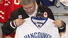 Canadian Prime Minister Stephen Harper looks over a Vancouver Canucks Jersey from Sport Chek in Richmond, British Columbia April 17, 2011. The jersey is for his son, Ben, who turns 15 this week. REUTERS/Ben Nelms (Ben Nelms/REUTERS/)