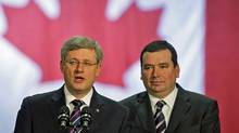 Prime Minister Stephen Harper and local MP Christian Paradis speak to workers at a plant in Thetford Mines, Que. on Dec. 13, 2010. (SHAUN BEST/Shaun Best/Reuters)
