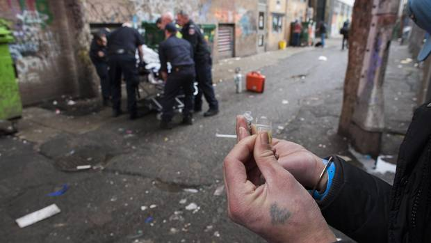 A drug user prepares a hit as first responders help an overdose victim in an alley in Vancouver's Downtown Eastside.