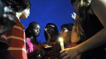 An impromtu candlelight vigil is started by young people, many in tears, during a news conference held by local politicians and faith leaders at the site ofn the Scarborough Housing complex shooting spree that occured last night, July 17, 2012. (J.P. Moczulski/The Globe and Mail)