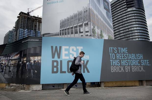 A pedestrian walks past a sign for West Block 1928 Condos in Toronto on May 27, 2017.