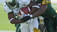 Edmonton Eskimos' T.J. Hill, 12, and Rennie Curran, centre, tackle the Saskatchewan Roughriders' Kory Sheets during first half CFL football game action in Edmonton, Alta., on Saturday, August 24, 2013. (John Ulan/THE CANADIAN PRESS)