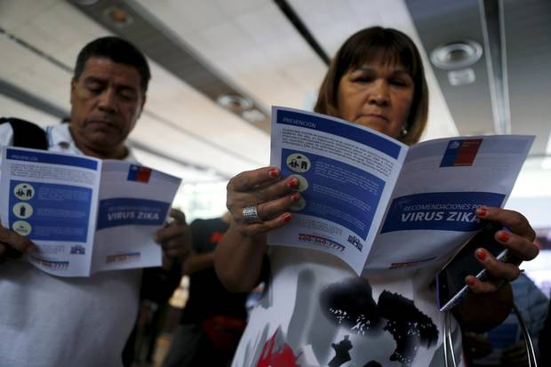 People read zika virus flyers from an information campaign by the Chilean Health Ministry at the departures area of Santiago's international airport, Chile January 28, 2016.