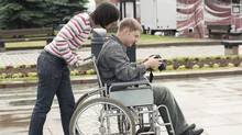 A young woman pushes a young man in a wheelchair. (Tatiana Belova/Tatiana Belova)